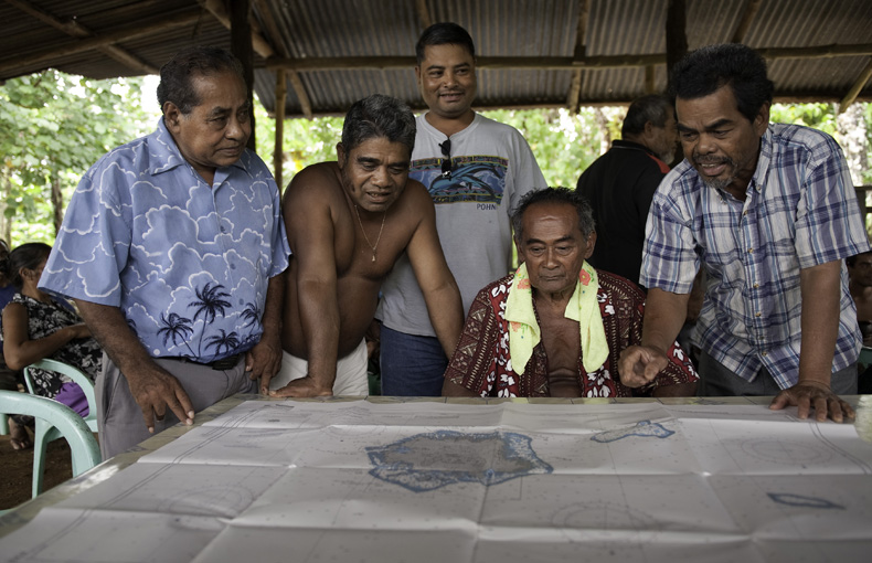 Kenopin David, the Mayor of Kitti Municipality, Nanid (esdepan Paulin), Patterson Shed, Director of the Conservation Society of Pohnpei, Joseph Santiago, one of Enipein's traditional chief, and Epert Mikel, one of Enipein's traditional chief discuss the future of Nahtik Marine Protected Area while looking over a nautical map of the island of Pohnpei. Photo © Nick Hall